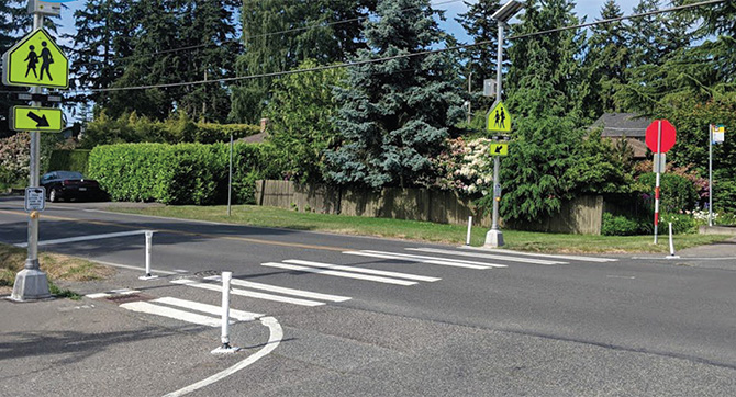 A marked crosswalk with flashing beacons installed and new painted curb extensions.