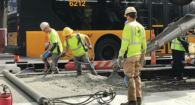 Construction workers pour concrete onto a road.